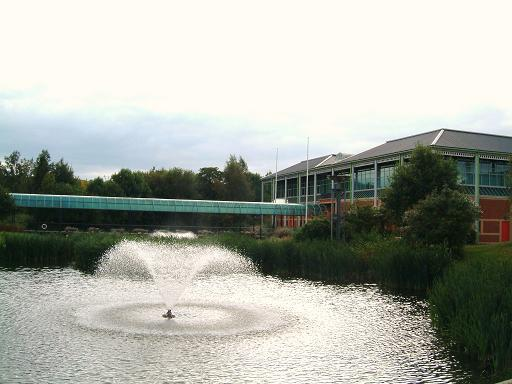 Photograph of a lake, fountain and building at the Loughborough campus