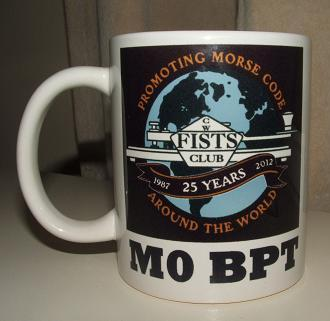 Photograph of the FISTS 25th Anniversary Mug with the black version of the anniversary logo and M0BPT printed underneath it